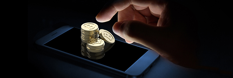 Finger point to golden coin currency tokens and mobile phone