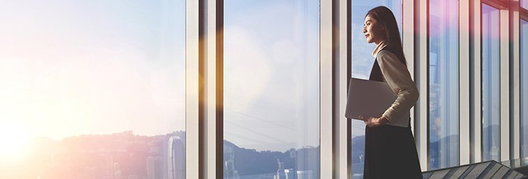 uccessful female office worker with net-book is standing in skyscraper interior against big window with city view on background